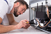 Photo Of Male Technician Repairing Refrigerator With Screwdriver