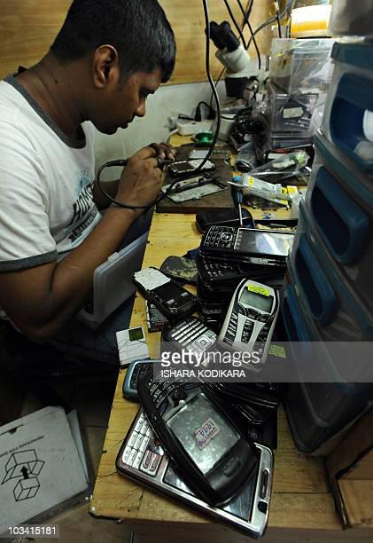 A technician repairs a mobile phone at his workshop in Colombo on May 12 2010 AFP PHOTO/Ishara SKODIKARA