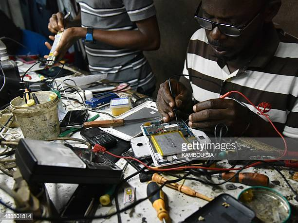 A technician repairs a mobile phone in a repair shop at the black market of the Koumassi quarter in Abidjan on August 12 2015 AFP PHOTO / KAMBOU SIA