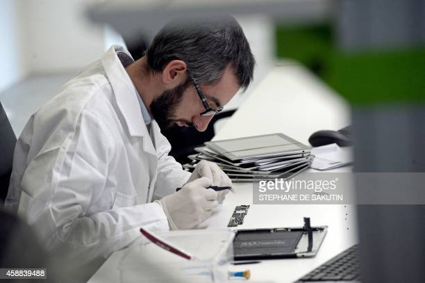 A technician repairs a tablet on November 7 2014 at the 'Allo Smartphone' company in Paris The company collects and repairs all kind of smartphones...