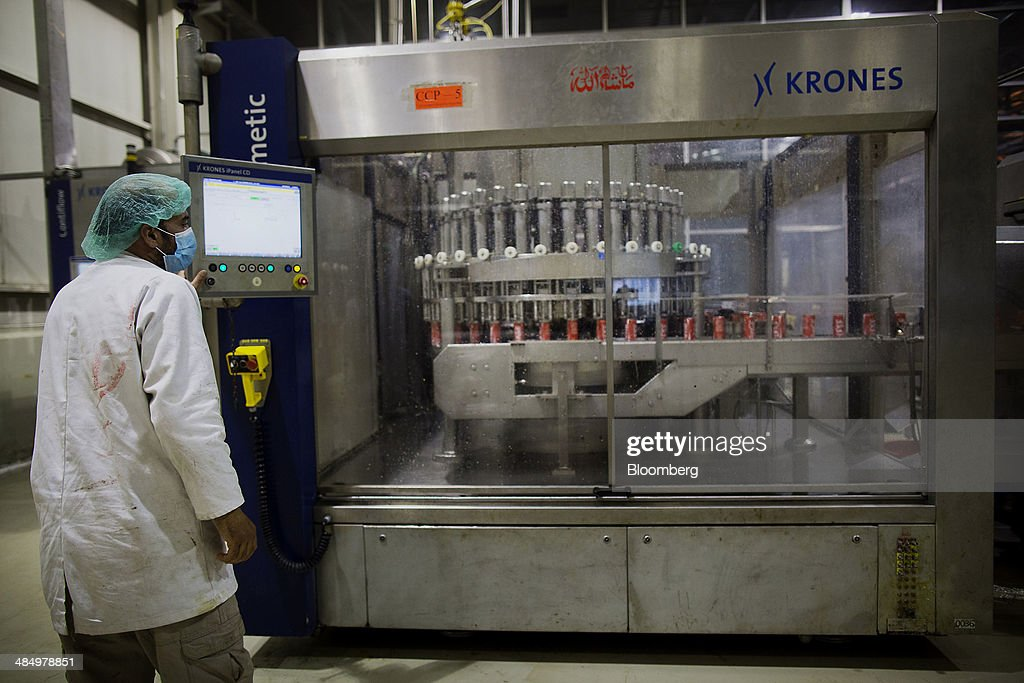 A technician runs a canning machine filling cans with Coca-Cola Co. beverage at the Habib Gulzar Non-Alcoholic Beverage Ltd. bottling facility in Kabul, Afghanistan, on Thursday, April 10, 2014. Coca-Cola Co., the world's largest soda maker, today showed signs of a rebound in the first three months of the year, easing the concerns that arose when the company unsettled investors with surprisingly sluggish global sales in the fourth quarter. Photographer: Victor J. Blue/Bloomberg via Getty Images