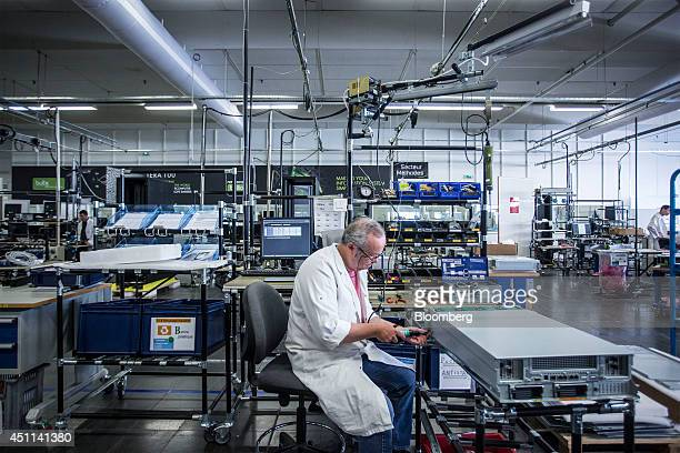 A technician screws down the casing for a Bullion computer server unit at the Bull SA headquarters in Angers France on Monday June 23 2014 Thierry...