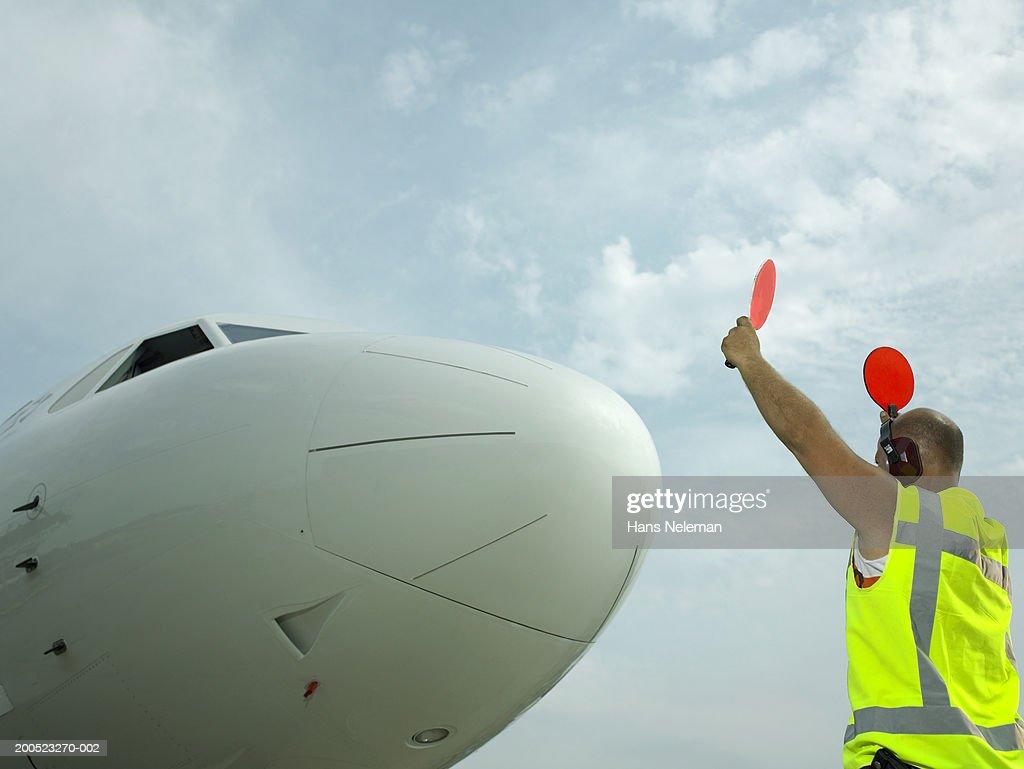 Technician signalling directions to aero plane