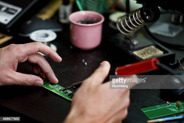 A technician solders a computer circuit board while using the workspace at the StartUp Lisboa Tech incubator for tech startups in Lisbon Portugal on...