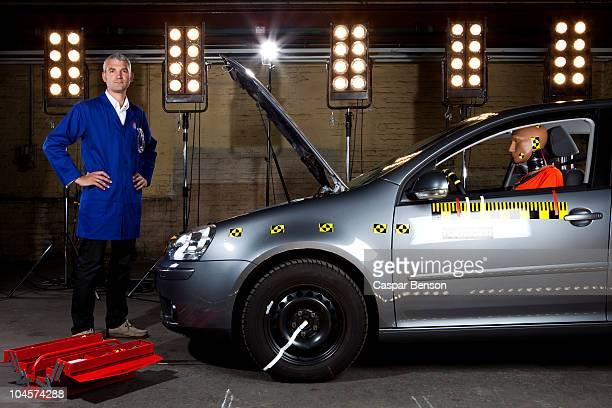 A technician standing next to a crash test car