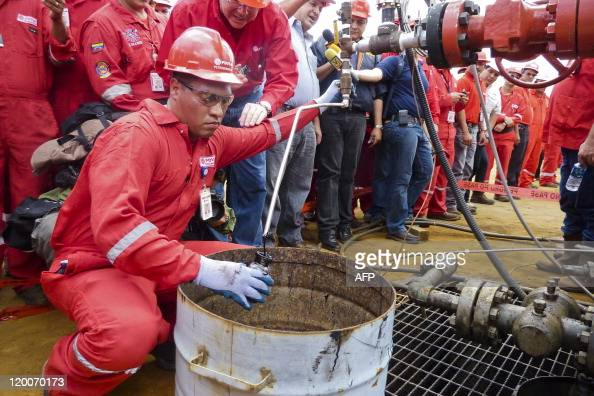 A technician takes a sample of crude oil from a well operated by Venezuela's stateowned oil company PDVSA in Morichal Venezuela on July 28 2011...