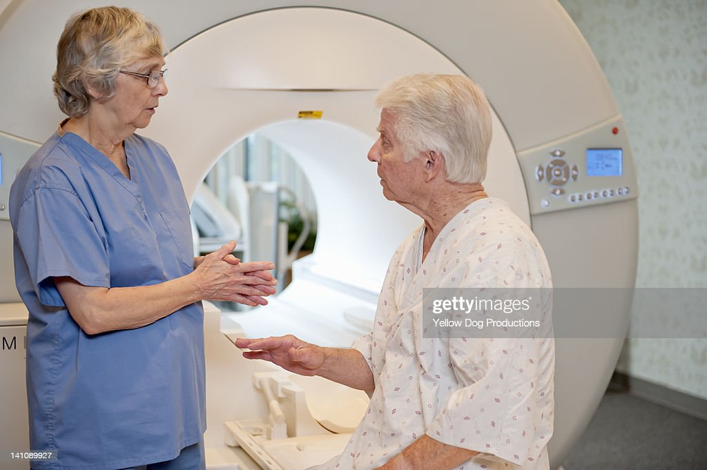 Technician talking to Patient at CT Scanner : Stock Photo