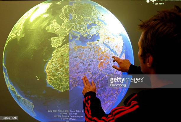 A technician tests a touchscreen version of the Google Earth map software called TouchEarth on a large monitor prior to the World Economic Forum in...