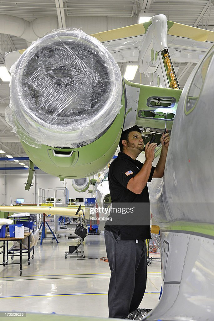 Technician Tom McCombs inspects the pylon of an Embraer SA Phenom 300 Light business jet at the company's executive jet manufacturing facility in Melbourne, Florida, U.S., on Monday, July 15, 2013. Embraer SA, the world's largest manufacturer of commercial jets up to 120 seats, delivered 22 jets to the commercial aviation market and 29 to the executive aviation market, for a total of 51 aircraft in the second quarter of 2013, according to a company press release. Photographer: Mark Elias/Bloomberg via Getty Images
