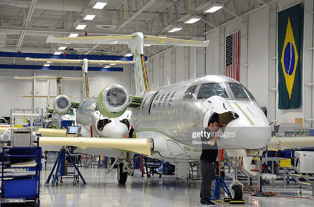 Technician Tom McCombs works on a cargo compartment of an Embraer Phenom 300 Light business jet at the company's executive jet manufacturing facility in Melbourne, Florida, U.S., on Monday, July 15, 2013. Embraer SA, the world's largest manufacturer of commercial jets up to 120 seats, delivered 22 jets to the commercial aviation market and 29 to the executive aviation market, for a total of 51 aircraft in the second quarter of 2013, according to a company press release. Photographer: Mark Elias/Bloomberg via Getty Images