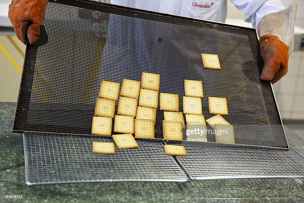 A technician transfers a sample of freshly-baked butter biscuits from a baking tray onto a cooling rack ahead of testing at Givaudan SA's flavor research center within the company's headquarters in Dubendorf, Switzerland, on Wednesday, Feb. 13, 2013. Givaudan SA, the world's largest maker of flavorings and fragrances, announced a bigger-than-estimated dividend after riding out a year of high raw-material prices and a strong Swiss franc. Photographer: Gianluca Colla/Bloomberg via Getty Images