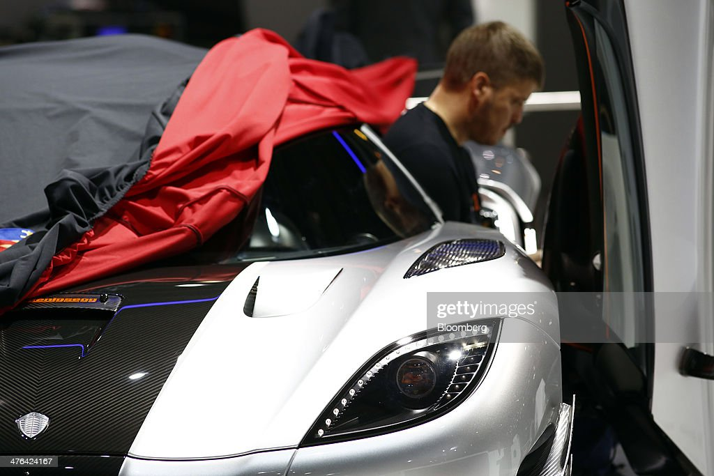 A technician uses a laptop computer as he sits in the doorwell of a Koenigsegg One:1 automobile, produced by Koenigsegg Automotive AB, on the company's stand ahead of the opening day of the 84th Geneva International Motor Show in Geneva, Switzerland, on Monday, March 3, 2014. The International Geneva Motor Show will run from Mar. 4, and showcase the latest models from the world's top automakers. Photographer: Gianluca Colla/Bloomberg via Getty Images