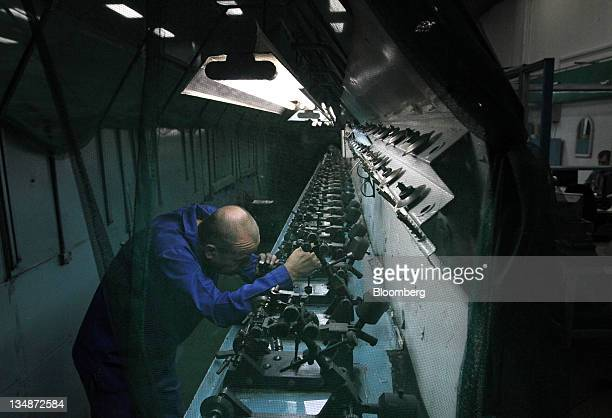 A technician uses a magnifier to inspect a natural diamond on a machine used for cutting at the Kristall Production Corp factory in Smolensk Russia...