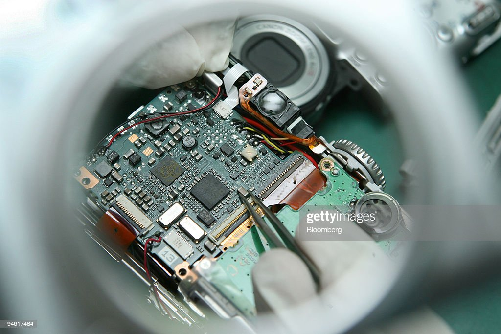 A technician uses tweezers under a magnifying glass to install electronic chips in a compact digital camera at Canon in Petaling Jaya, Malaysia, on Monday, Jan. 7, 2008. Malaysia's export growth probably slowed in December as a cooling U.S. economy and a rising ringgit hurt demand for the Southeast Asian nation's electronics goods.