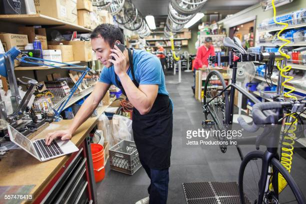 Technician using cell phone and laptop in bicycle repair shop