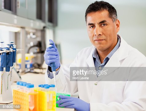Technician using pipette in hematology lab