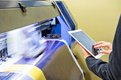 Technician using tablet control with format large inkjet printing blue plate
