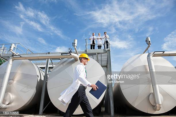 Technician walking by tanks outdoors