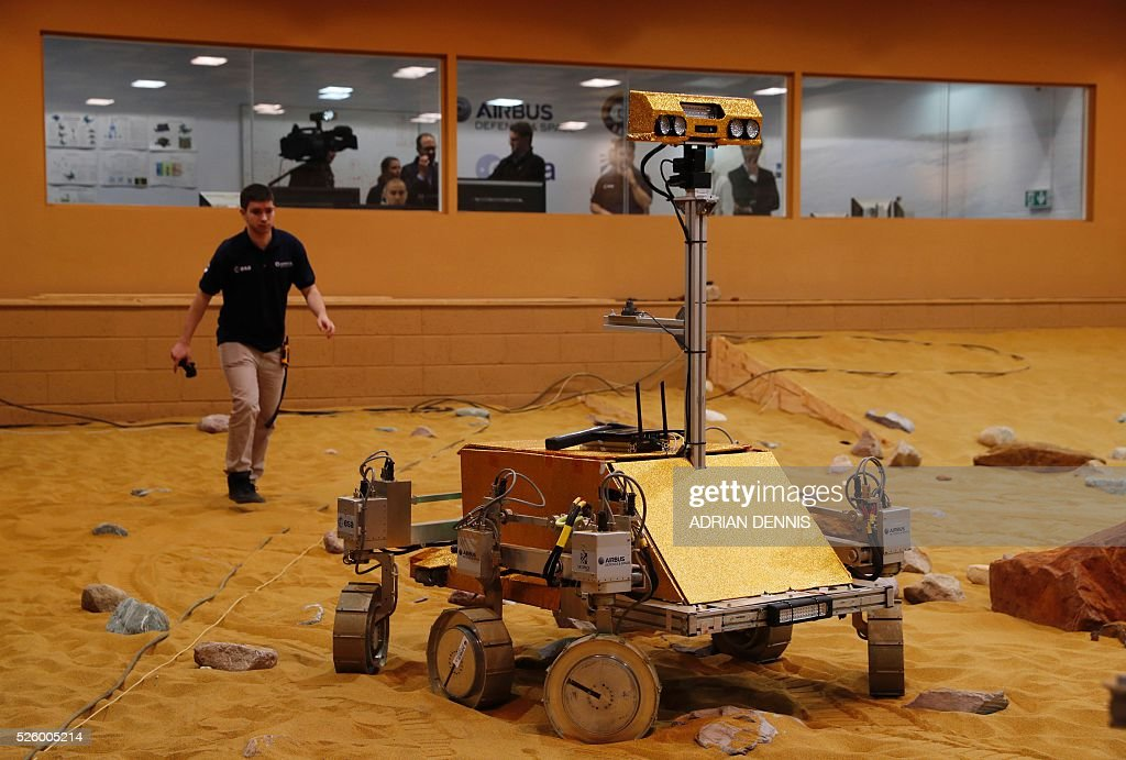 A technician walks toward a prototype Mars rover in a simulated Mars environment at the Airbus Defence and Space company in Stevenage on April 29, 2016. British astronaut Major Tim Peake will remotely navigate the rover through the Martian landscape from the International Space Station, part of a project to learn how astronauts can control remote systems. / AFP / ADRIAN
