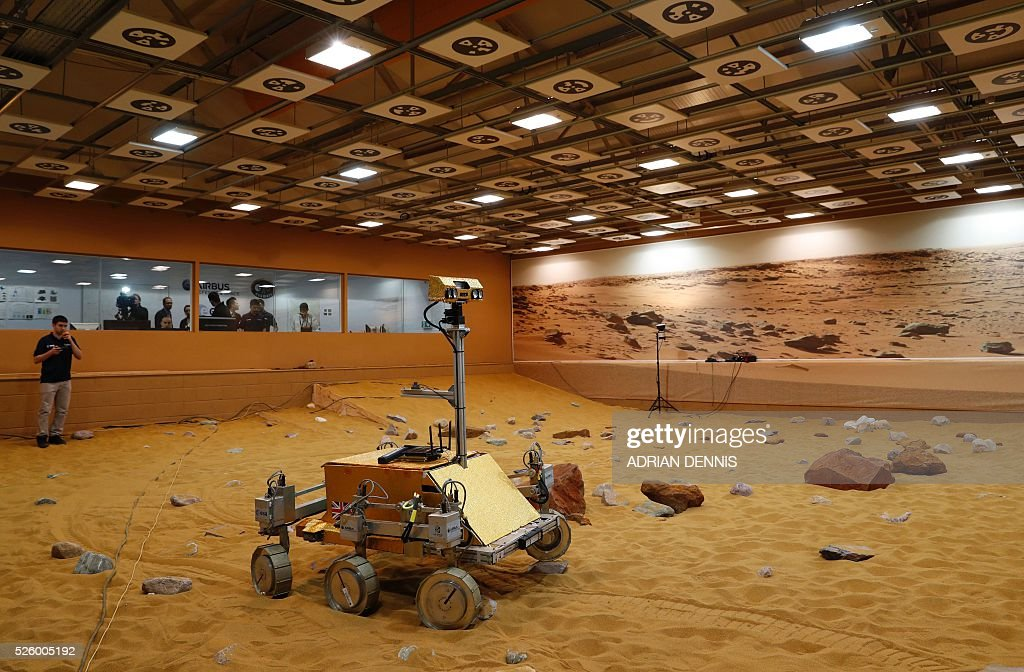 A technician watches a prototype Mars rover in a simulated Mars environment at the Airbus Defence and Space company in Stevenage on April 29, 2016. British astronaut Major Tim Peake will remotely navigate the rover through the Martian landscape from the International Space Station, part of a project to learn how astronauts can control remote systems. / AFP / ADRIAN