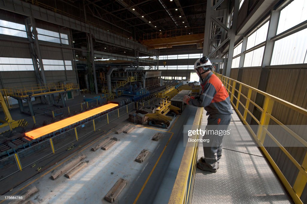 A technician watches as a red hot steel bar moves along the production line in the hot strip shop at the ArcelorMittal Poland SA steel mill in Krakow, Poland, on Tuesday, Aug. 6, 2013. ArcelorMittal, the biggest steelmaker globally and in Poland, said on March 15 it expects European demand to slide before rebounding in 2014. Photographer: Will Boase/Bloomberg via Getty Images