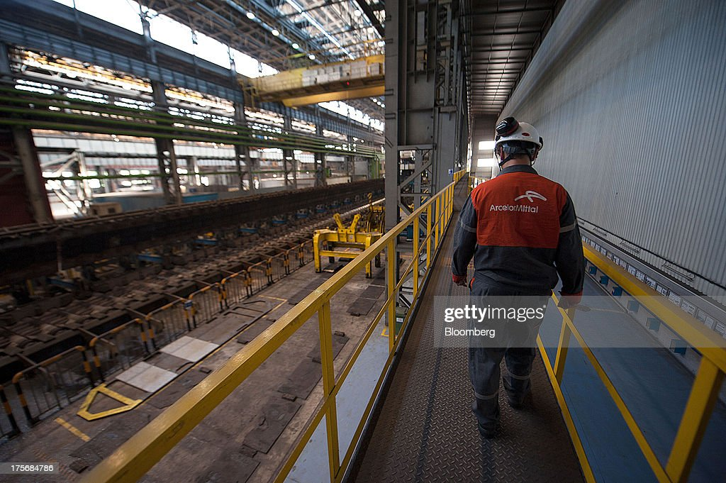 A technician wears a company logo as he walks along the production line in the hot strip shop at the ArcelorMittal Poland SA steel mill in Krakow, Poland, on Tuesday, Aug. 6, 2013. ArcelorMittal, the biggest steelmaker globally and in Poland, said on March 15 it expects European demand to slide before rebounding in 2014. Photographer: Will Boase/Bloomberg via Getty Images
