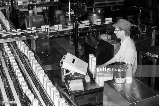 A technician weighs milk cartons to ensure the correct volume in each at a new 12million Unigate Dairy in Shepherds Bush west London