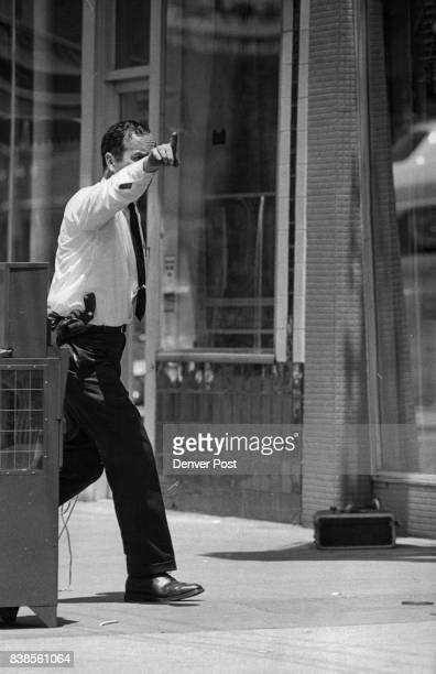 Technician William B Smith of the Denver Police Bomb Squad orders S Broadway closed and businesses cleared after peek into suitcase leads him to...
