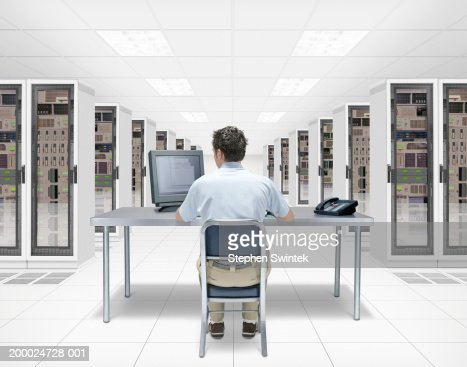IT technician working at desk in server room (Digital Composite) : Photo