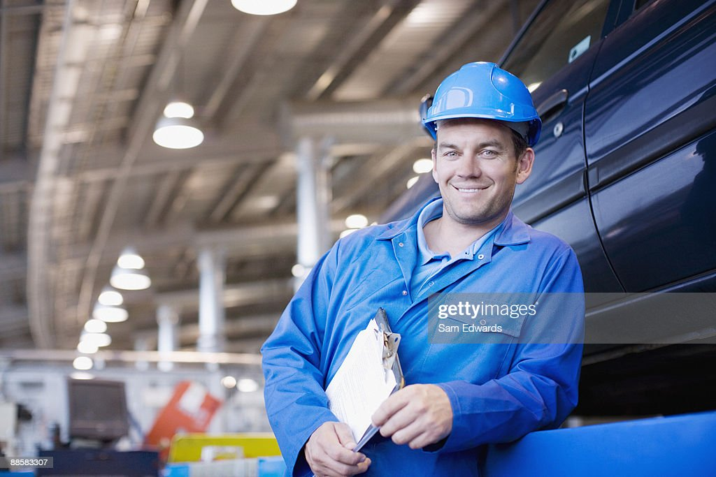 Technician working in auto shop : Stock Photo