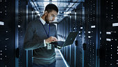 IT Technician Works on a Laptop in Big Data Center full of Rack Servers. He Runs Diagnostics and Maintenance, Sets up System.