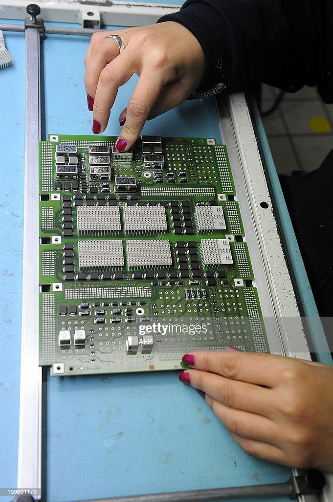A technician works on a printed circuit boards designed for cars onboards electronic on January 18, 2013 in Colomiers, southwestern France, in the French Automotive Equipment Manufacturer Actia, specialized in electronic automotive. Actia has been labelled today as the main supplier of French car manufacturer PSA Peugeot Citroen. Actia will be one of the 100 main suppliers of PSA Citroen within the next two years. GABALDA