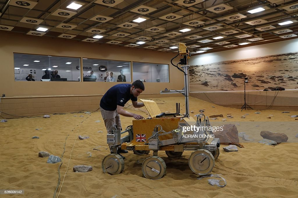 A technician works on a prototype Mars rover in a simulated Mars environment at the Airbus Defence and Space company in Stevenage on April 29, 2016. British astronaut Major Tim Peake will remotely navigate the rover through the Martian landscape from the International Space Station, part of a project to learn how astronauts can control remote systems. / AFP / ADRIAN