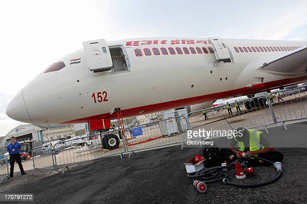 A technician works on the tarmac in front of a Boeing Co 7878 Dreamliner aircraft operated by Air India Ltd on the second day of the Paris Air Show...