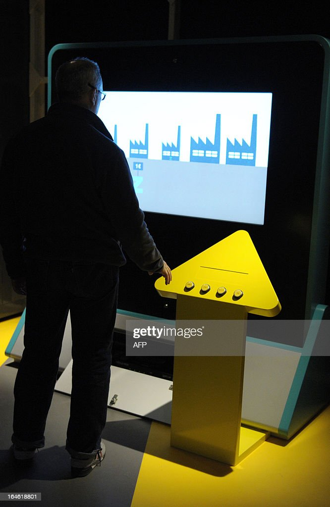A technician works to prepare an animation screen on March 25, 2013 prior to the opening of the exhibition 'L'Economie: krach, boom, mue ?' at the Cite des Sciences in Paris
