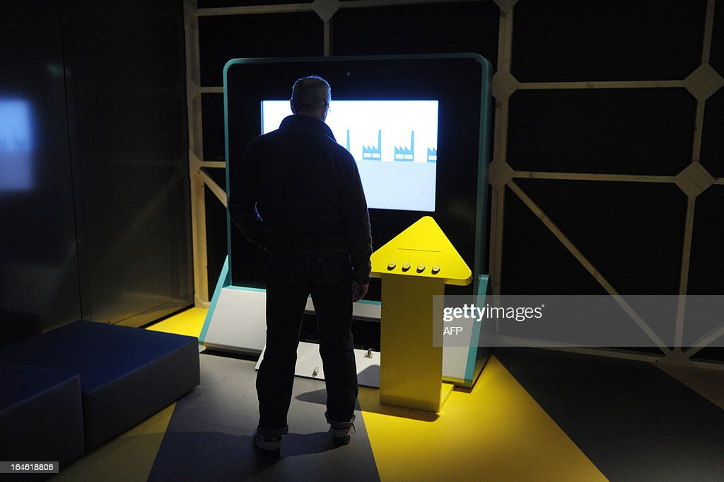 A technician works to prepare an animation screen on March 25, 2013 prior to the opening of the exhibition 'L'Economie: krach, boom, mue ?' at the Cite des Sciences in Paris AFP PHOTO ERIC PIERMONT