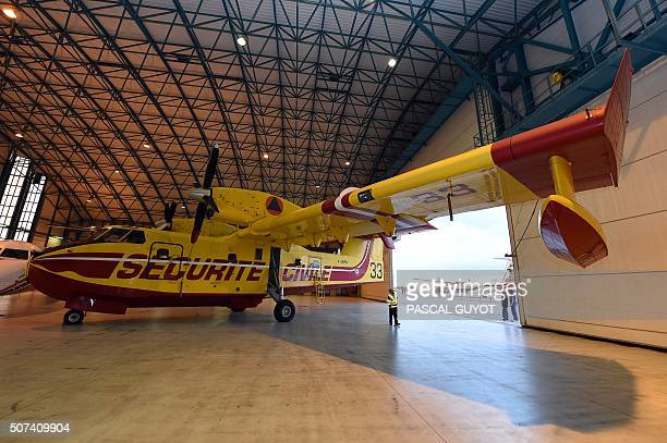 Technicians check a Canadair plane in a hangar during the NimesGarons civil security air force base's inauguration on January 29 2016 in Nimes...