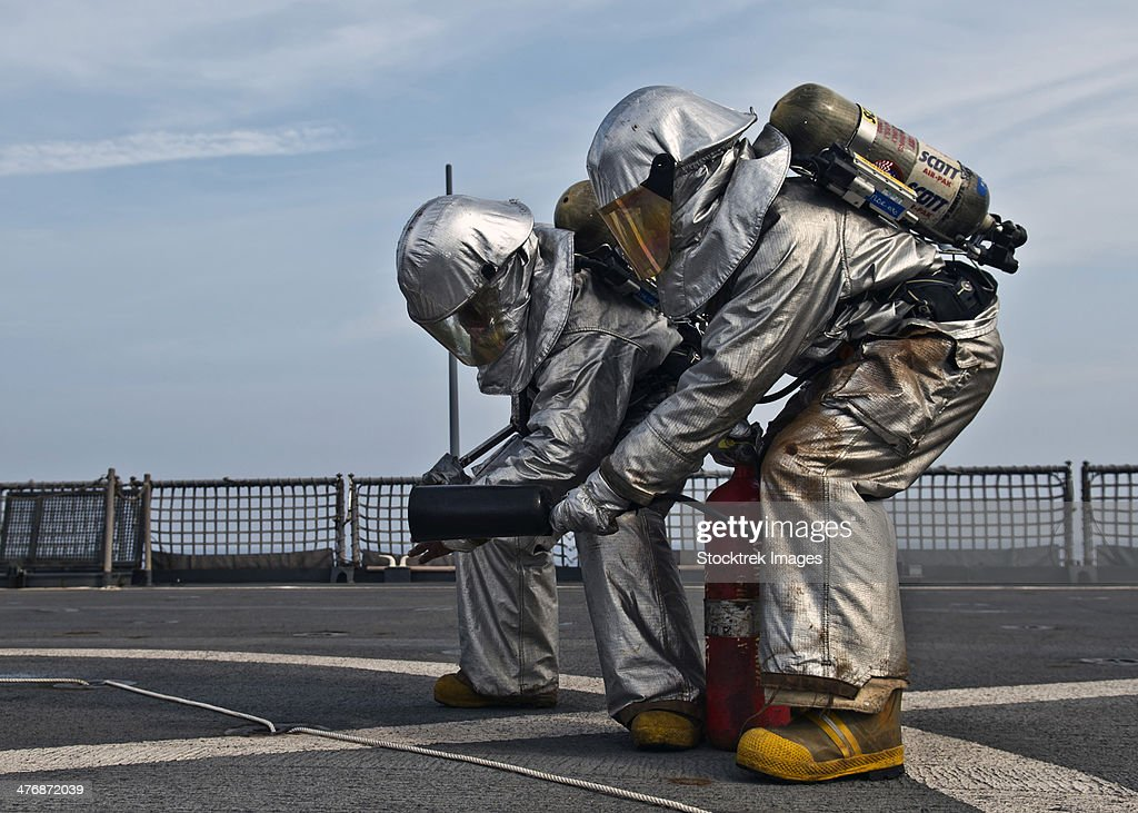 Technicians check for hot spots during a firefighting drill aboard USS Tortuga.