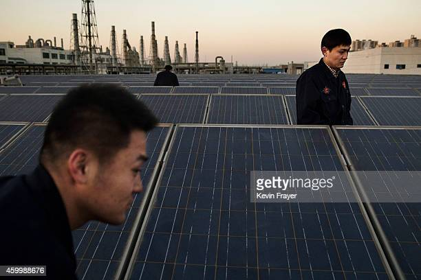 Technicians from Yingli Solar check solar panels used to produce energy for lighting on the roof at the company's headquarters on December 4 2014 in...
