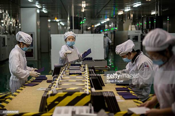 Technicians from Yingli Solar work in the final preparations of solar cells used for solar panels at the company's headquarters on December 4 2014 in...