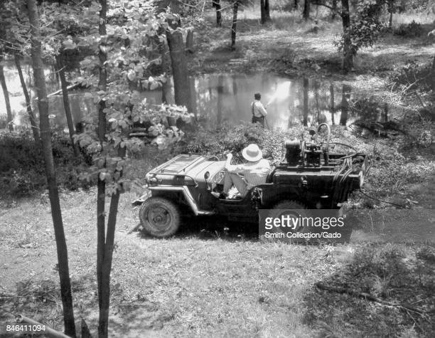 Technicians in a Jeep parked beside a lake spray the surface of the lake with oil an early method for controlling mosquito larvae by suffocating them...