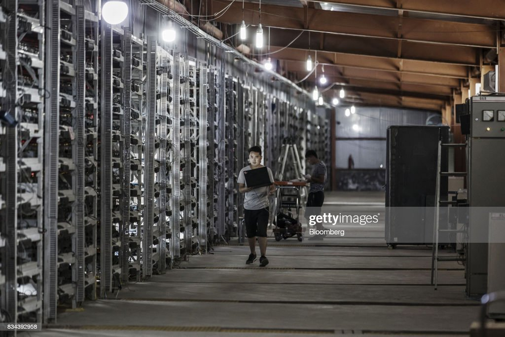 Technicians inspect bitcoin mining machines at a mining facility operated by Bitmain Technologies Ltd. in Ordos, Inner Mongolia, China, on Friday, Aug. 11, 2017. Bitmain is one of the leading producers of bitcoin-mining equipment and also runs Antpool, a processing pool that combines individual miners from China and other countries, in addition to operating one of the largest digital currency mines in the world. Photographer: Qilai Shen/Bloomberg via Getty Images