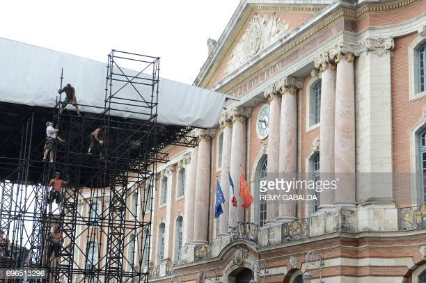 Technicians install a stage on the Place du Capitole in Toulouse on June 15 ahead of a show broadcast live by French TV channel France 2 for the...
