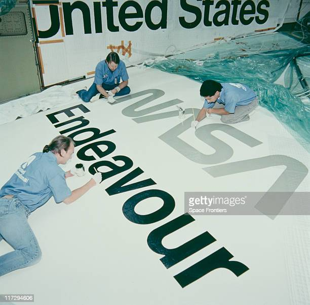 Technicians painting the insignia on parts of the Space Shuttle Endeavor during its construction at Rockwell International Space Transportation...