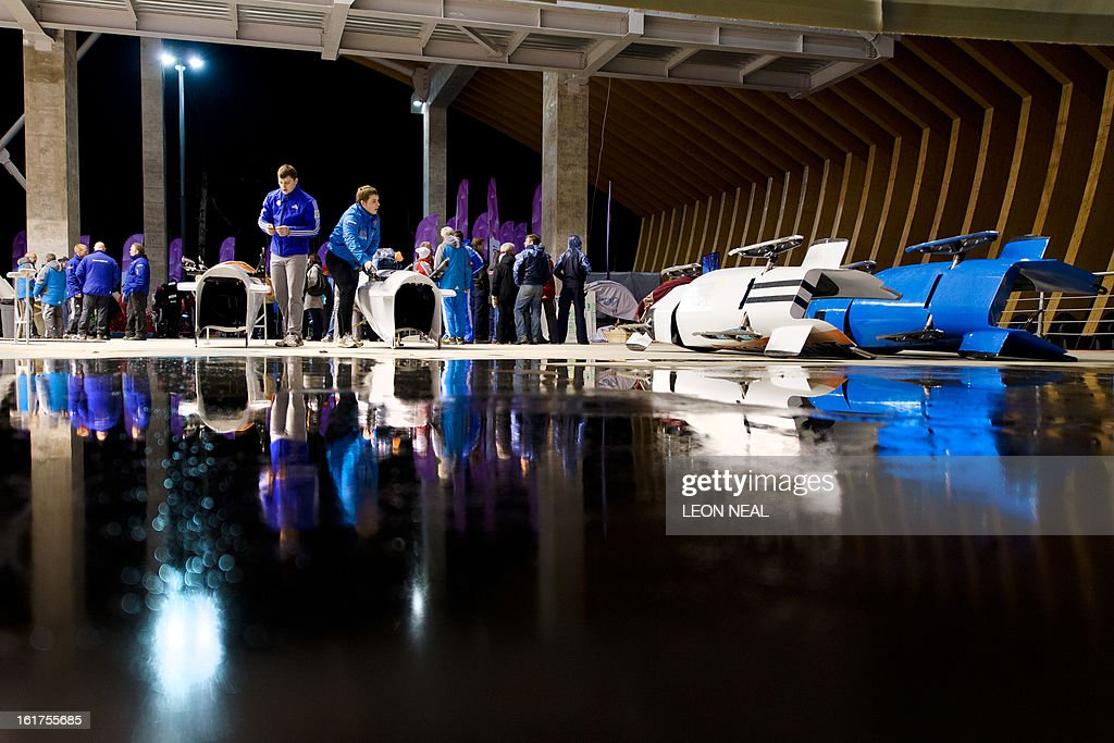 Technicians prepare bobsleighs for the Russian team during the Women's Bobsleigh competition at the Sanki Sliding Centre, some 50 km from Russia's Black Sea resort of Sochi, on February 15, 2013. With a year to go until the Sochi 2014 Winter Games, construction work continues as tests events and World Championship competitions are underway.