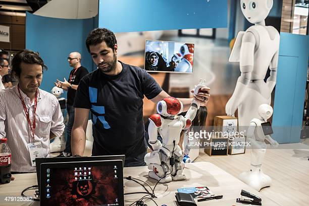 Technicians program a humanoid robot at the fifth edition of the European fair 'Innorobo' dedicated to robotics technologies in Lyon southeastern...