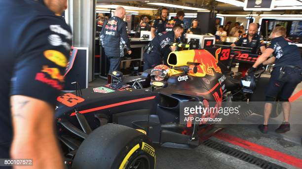 Technicians push the car of Red Bull's Dutch driver Max Verstappen into the paddock during the second practice session of the Formula One Azerbaijan...