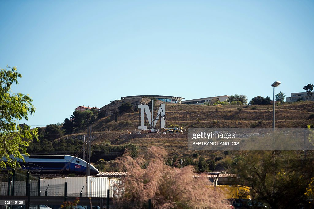 Technicians set up on the side of a hill the first large letter in the title of a series called 'Marseille' to be broadcast in the near future by the streaming video giant Netflix, on May 4, 2016 in Marseille, southern France. The series, made up of eight episodes, is a political drama set in this city starring among others French actor Gerard Depardieu and will be available on the Netflix platform from May 5. The first two episodes will also be shown on TF1, a French private national TV channel. / AFP / BERTRAND