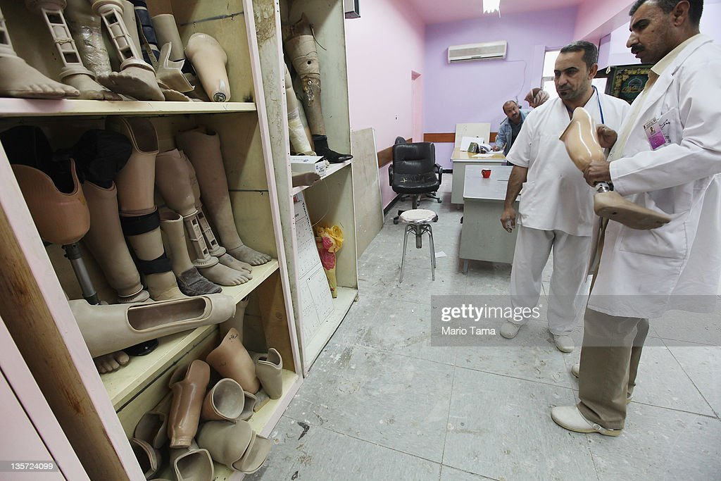 Technicians stand next to prosthetics at the Factory of Prosthetic Limbs on December 13, 2011 in Baghdad, Iraq. Wounded Iraqis face a shortage of the outdated prosthetics due to a spike in war-related injuries in recent years. Iraq's health care system remains in shambles following two decades of war and economic sanctions. Following the 2003 U.S. invasion, thousands of physicians fled the country while others were killed. Some physicians have since returned but there is still a critical shortage of doctors. Iraq is transitioning nearly nine years after the 2003 U.S. invasion and subsequent occupation. American forces are now in the midst of the final stage of withdrawal from the war-torn country. At least 4,485 U.S. military personnel have died in service in Iraq. According to the Iraq Body Count, more than 100,000 Iraqi civilians have died from war-related violence.