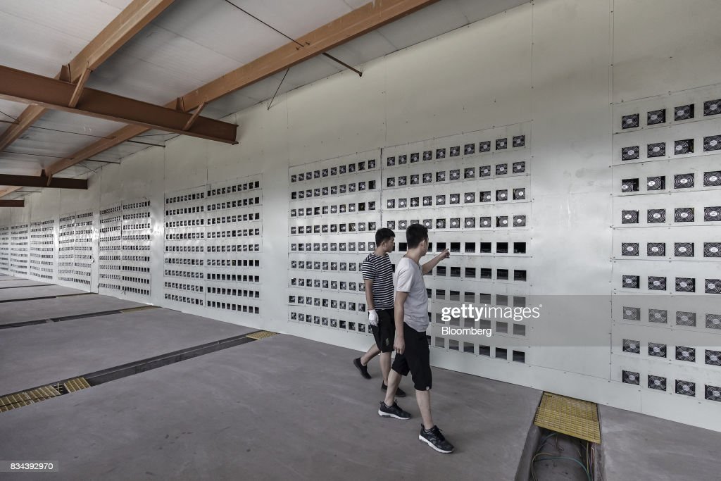 Technicians walk through a cooling chamber adjacent to a wall of bitcoin mining machines at a mining facility operated by Bitmain Technologies Ltd. in Ordos, Inner Mongolia, China, on Friday, Aug. 11, 2017. Bitmain is one of the leading producers of bitcoin-mining equipment and also runs Antpool, a processing pool that combines individual miners from China and other countries, in addition to operating one of the largest digital currency mines in the world. Photographer: Qilai Shen/Bloomberg via Getty Images